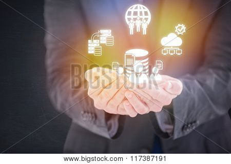 Handsome businessman presenting with hands against dark room