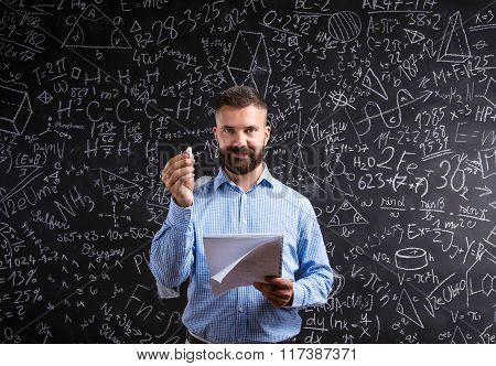 Teacher with notebook against big blackboard with symbols and fo