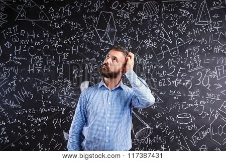 Teacher scratching his head against big blackboard with mathemat