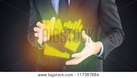 Mid section of a businessman presenting with his hands against dark room