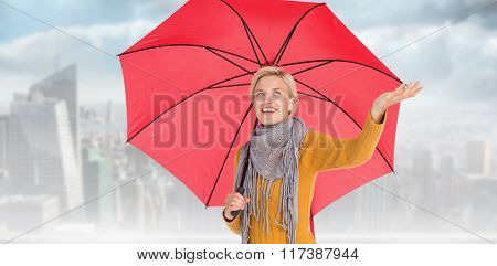 Woman checking to see if its raining against balcony overlooking city