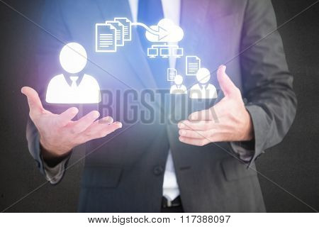 Handsome businessman presenting with hands against grey room