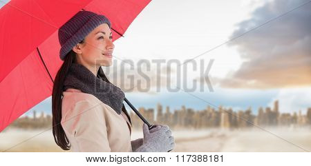 Smiling brunette holding red umbrella against path in yellow field leading to city