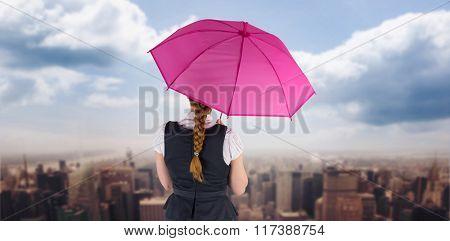 Pretty redhead businesswoman holding umbrella against new york