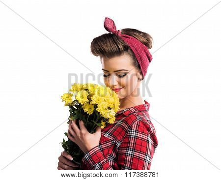 Woman with pin-up make-up and hairstyle smelling yellow daisies