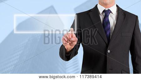 Businessman in suit pointing finger against skyscraper