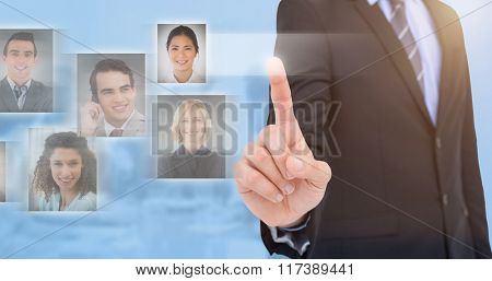 Mid section of businessman pointing something up against blue background
