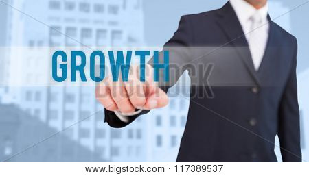The word growth and smiling businessman in suit pointing against low angle view of city buildings