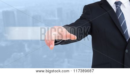 Businessman in suit pointing his finger against view of cityscape