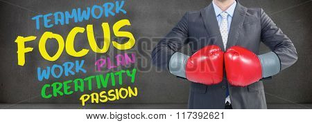 Businessman with boxing gloves against buzz words in room