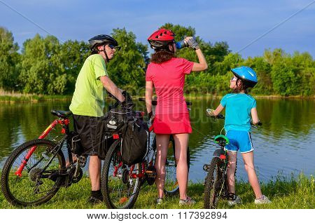 Family bike ride outdoors, active parents and kid cycling and relaxing near beautiful river