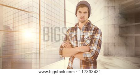 Portrait of confident hipster with arms crossed against modern room overlooking city