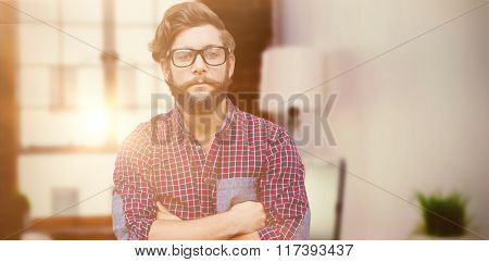 Confident hipster wearing eye glasses with arms crossed against laptop on desk with glasses and notepad