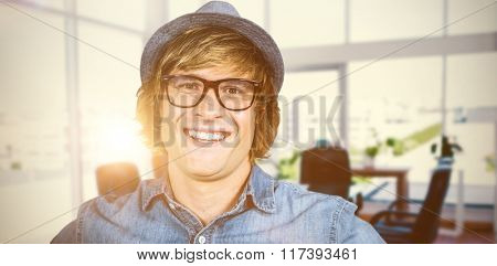 Smiling blond hipster staring at camera against board room