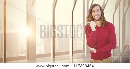 Portrait of happy hipster holding pen against room with large window looking on city