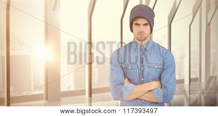 Portrait of serious hipster with arms crossed against room with large window looking on city