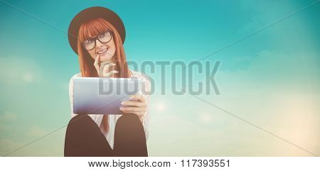 Smiling hipster woman using her tablet against blue green background