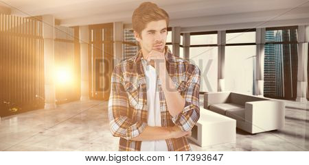 Confident businessman standing with hand on chin against modern room overlooking city