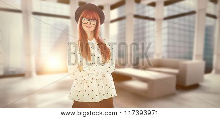 Portrait of a smiling hipster woman with arms crossed against modern room overlooking city