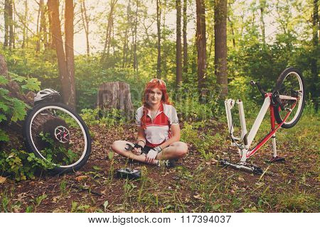 Young Sportswoman Bicyclist Repairing Her Mtb Bike In The Forest