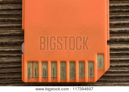 Orange memory SD card, old wood background