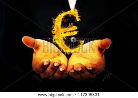 Businessman holding his hands out against dark background