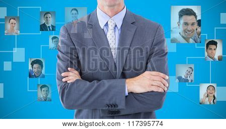 Portrait of smiling businessman standing hands folded against blue background with vignette