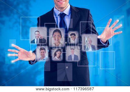 Businessman standing with fingers spread out against blue background with vignette