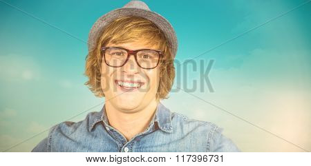 Smiling blond hipster staring at camera against blue green background