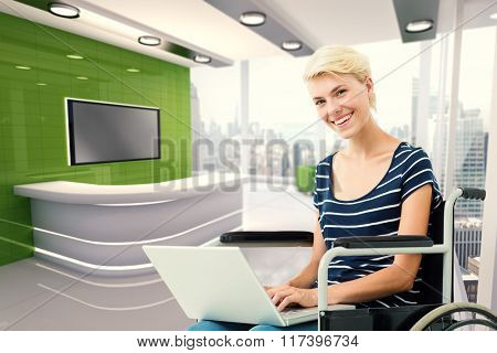 Woman in wheelchair using computer against modern room overlooking city