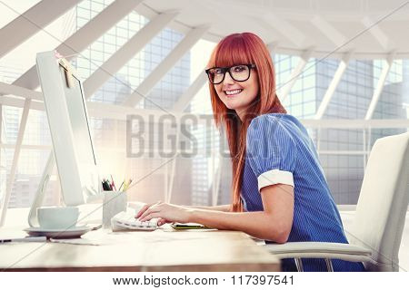 Smiling hipster woman typing on keyboard against modern room overlooking city