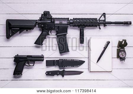 Rifle, Gun, Knife, Compass And Notebook On The Table