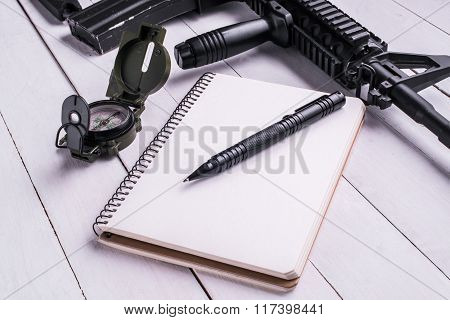 Assault Rifle,compass, Notebook With Pen On Desk.