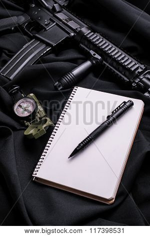 Notepad With Pen On Black Cloth With Rifle And Compass