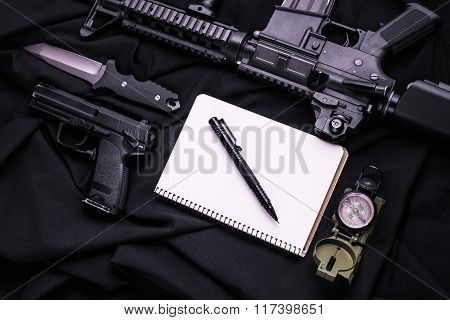 Weapon, Notebook, Pen, Knife And Compass On Black Fabric.