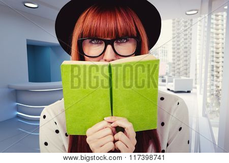 Hipster woman behind a green book against modern room overlooking city