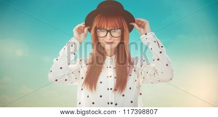 Attractive smiling hipster woman with hat against blue green background