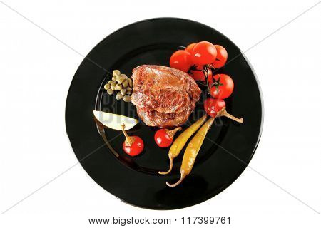 grilled meat medallion served with tomatoes on black