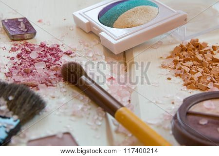 Women Accessories Cosmetics. Makeup Brushes And Crushed Eyeshadow On Wooden Background