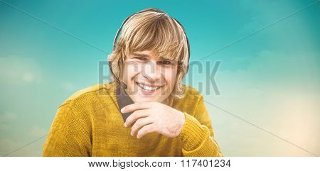 Smiling hipster businessman using headset against blue green background