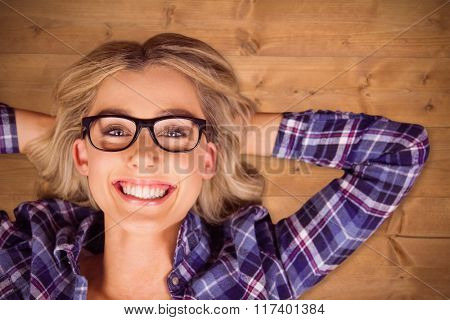 Portrait of gorgeous smiling blonde hipster lying against bleached wooden planks background