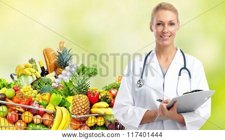 Doctor woman near shopping cart with food.