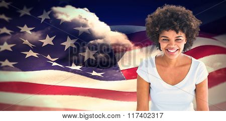 Smiling woman posing on white background against composite image of digitally generated american flag rippling