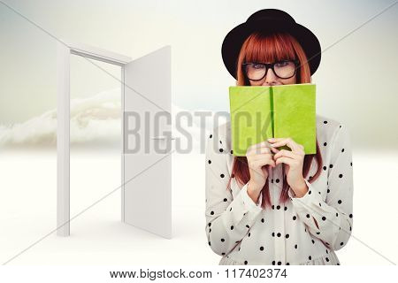 Hipster woman behind a green book against open door in sky