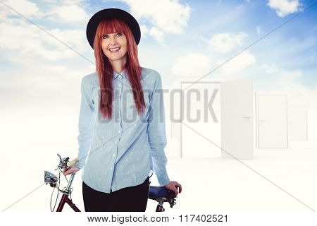 Smiling hipster woman leaning on a bike against opening door in sky