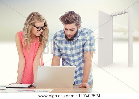 Man using laptop while discussing with woman at desk against open door in sky
