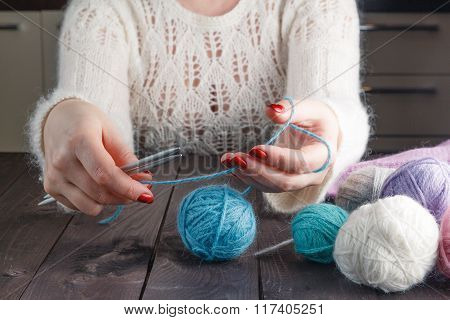 Woman Is Knitting On A Kitchen Table