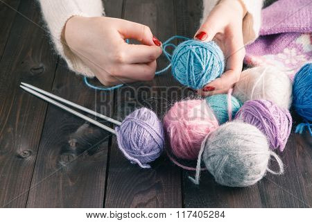 Female Hands With Purple Manicure Are Knitted Metal Spokes Of A Wooden Table.