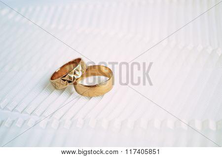 Two Golden Wedding Rings On Light Ribbon Background