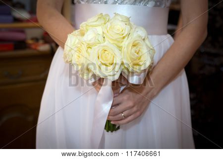 Bride holding white wedding bouquet of roses